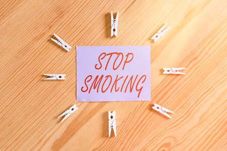 Handwriting text Stop Smoking. Conceptual photo the process of discontinuing or quitting tobacco smoking Colored clothespin papers empty reminder wooden floor background office