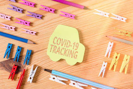 Word writing text Covid 19 Tracking. Business photo showcasing Distinguishing process of the possible infected individuals Colored clothespin papers empty reminder wooden floor background office