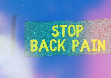 Writing note showing Stop Back Pain. Business concept for put an end on the pain felt in the low or upper back Rolled ripped torn cardboard above a wooden classic table