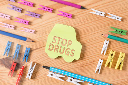 Word writing text Stop Drugs. Business photo showcasing put an end on the dependence on substances such as heroin or cocaine Colored clothespin papers empty reminder wooden floor background office