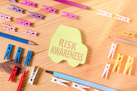 Word writing text Risk Awareness. Business photo showcasing recognizing factors that may cause a lifethreatening effect Colored clothespin papers empty reminder wooden floor background office Фото со стока