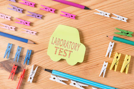 Word writing text Laboratory Test. Business photo showcasing Determination of a medical diagnosis from the substances tested Colored clothespin papers empty reminder wooden floor background office Фото со стока