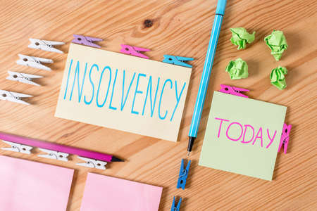Handwriting text writing Insolvency. Conceptual photo the state of being insolvent inability to pay one s is debts Colored clothespin papers empty reminder wooden floor background office