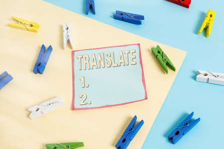 Word writing text Translate. Business photo showcasing bear, remove, or change from one place, state, form, or appearance Colored clothespin paper empty reminder yellow blue floor background office