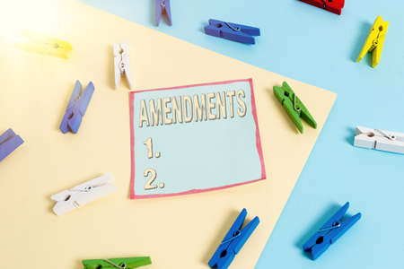 Word writing text Amendments. Business photo showcasing process of amending a law or document by parliamentary. Colored clothespin paper empty reminder yellow blue floor background office