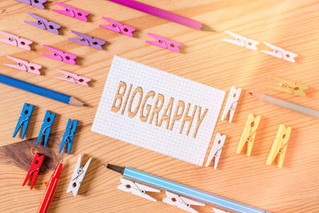 Conceptual hand writing showing Biography. Concept meaning an account of the life of something such as an animal, a coin, etc. Colored crumpled papers wooden floor background clothespin
