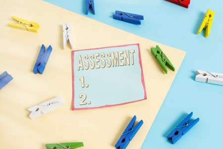 Word writing text Assessment. Business photo showcasing action or an instance of making a judgment about something Colored clothespin paper empty reminder yellow blue floor background office Imagens