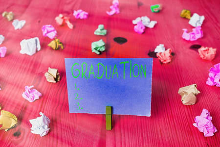 """写写""""毕业""""的纸条。学历或文凭的奖励或验收的企业概念色弄皱了长方形形状的提示纸浅兰的背景"""