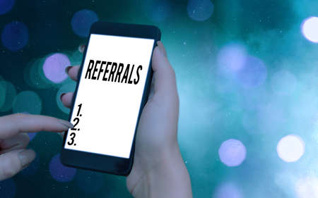 Conceptual hand writing showing Referrals. Concept meaning act, action, or an instance of referring to someone for work Modern gadgets white screen under colorful bokeh background