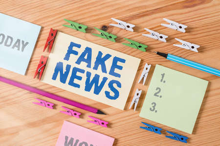 Word writing text Fake News. Business photo showcasing false information publish under the guise of being authentic news Colored clothespin papers empty reminder wooden floor background office Archivio Fotografico