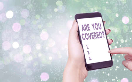 Text sign showing Are You Covered Question. Business photo text asking if they had insurance in work or life Modern gadgets with white display screen under colorful bokeh background