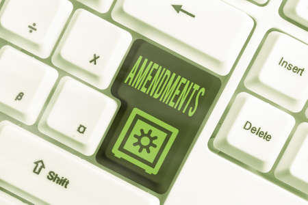 Text sign showing Amendments. Business photo showcasing process of amending a law or document by parliamentary. Different colored keyboard key with accessories arranged on empty copy space