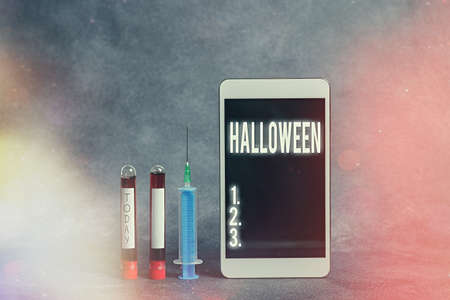 Text sign showing Halloween. Business photo showcasing October 31 observed especially with dressing up in disguise Extracted blood sample vial with medical accessories ready for examination