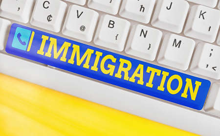 Conceptual hand writing showing Immigration. Concept meaning the action of coming to live permanently in a foreign country Colored keyboard key with accessories arranged on empty copy space