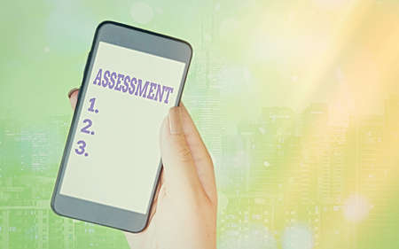 Writing note showing Assessment. Business concept for action or an instance of making a judgment about something Modern gadgets white screen under colorful bokeh background