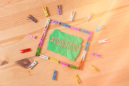 Conceptual hand writing showing Acquisition. Concept meaning asset or object bought or obtained, typically by a library Colored crumpled papers wooden floor background clothespin