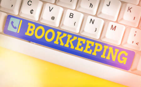 Conceptual hand writing showing Bookkeeping. Concept meaning keeping records of the financial affairs of a business Colored keyboard key with accessories arranged on empty copy space