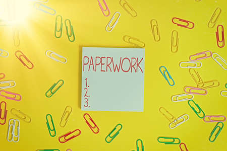 Writing note showing Paperwork. Business concept for routine clerical or recordkeeping work often incidental Flat lay above empty paper with copy space and colored paper clips