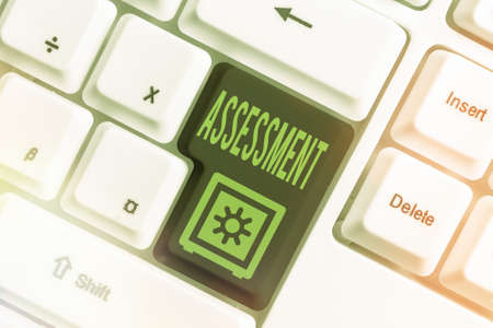 Text sign showing Assessment. Business photo showcasing action or an instance of making a judgment about something Different colored keyboard key with accessories arranged on empty copy space