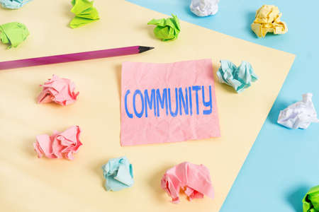 Conceptual hand writing showing Community. Concept meaning with a common characteristic or interest living together Colored crumpled papers empty reminder blue yellow clothespin
