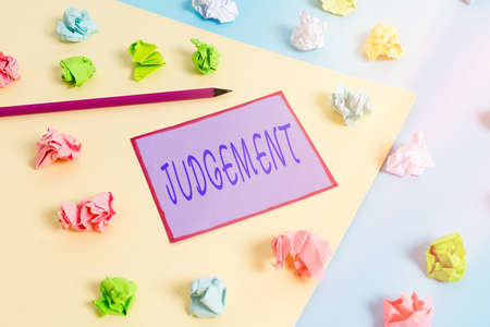 Conceptual hand writing showing Judgement. Concept meaning process of forming an evaluation by discerning and comparing Colored crumpled papers empty reminder blue yellow clothespin Imagens