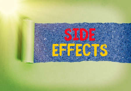 Handwriting text Side Effects. Conceptual photo Typically undesirable effect of a drug or medical treatment Rolled ripped torn cardboard placed above a wooden classic table backdrop Foto de archivo