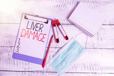 Conceptual hand writing showing Liver Damage. Concept meaning any disorder of the liver Cirrhosis or scarring of the liver Blood sample vial medical accessories ready for examination