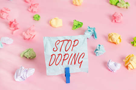 Writing note showing Stop Doping. Business concept for quit the use of banned athletic performanceenhancing drugs Colored crumpled papers empty reminder pink floor background clothespin