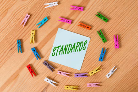 Writing note showing Standards. Business concept for something established by authority, custom, or general consent Colored clothespin papers empty reminder wooden floor background office