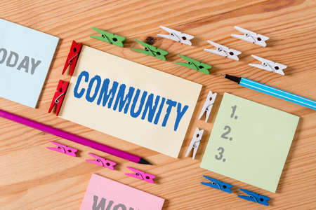 Word writing text Community. Business photo showcasing group of showing with a common characteristics living together Colored clothespin papers empty reminder wooden floor background office