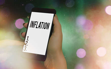 Conceptual hand writing showing Inflation. Concept meaning increase in the volume of money relative to available goods Modern gadgets white screen under colorful bokeh background 版權商用圖片