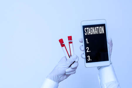 Handwriting text writing Stagnation. Conceptual photo condition marked by lack of flow, movement, or development Extracted blood sample vial with lastest technology ready for examination 스톡 콘텐츠