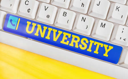 Conceptual hand writing showing University. Concept meaning institution of higher learning providing facilities for teaching Colored keyboard key with accessories arranged on empty copy space