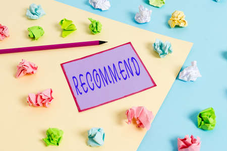 Conceptual hand writing showing Recommend. Concept meaning present as worthy of acceptance or trial, make acceptable Colored crumpled papers empty reminder blue yellow clothespin