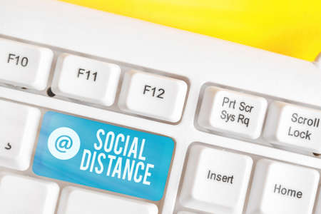 Writing note showing Social Distance. Business concept for maintaining a high interval physical distance for public health safety Colored keyboard key with accessories arranged on empty copy space