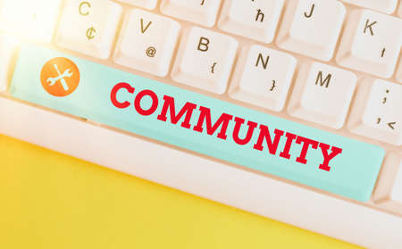 Handwriting text Community. Conceptual photo with a common characteristic or interest living together Different colored keyboard key with accessories arranged on empty copy space Imagens