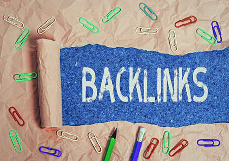 Text sign showing Backlinks. Business photo text links from one website to a page on another website or page Rolled ripped torn cardboard placed above a wooden classic table backdrop