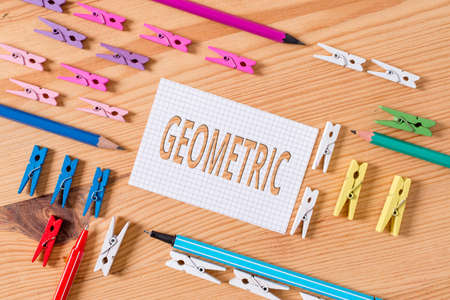 Conceptual hand writing showing Geometric. Concept meaning using straight or curved lines in designs and many more. Colored crumpled papers wooden floor background clothespin 写真素材