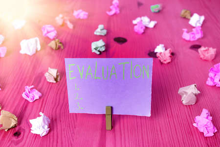 Writing note showing Evaluation. Business concept for the making of judgment about the amount or value of something Colored crumpled rectangle shaped reminder paper light blue background