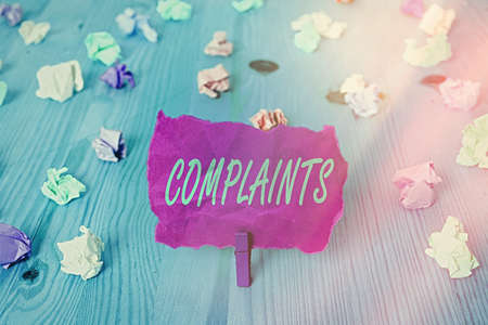 Text sign showing Complaints. Business photo text something that is the cause or subject of protest or outcry Colored crumpled rectangle shaped reminder paper light blue background Stock Photo