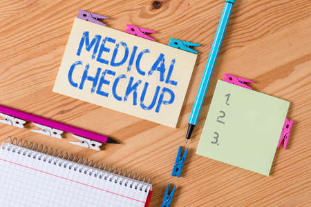 Conceptual hand writing showing Medical Checkup. Concept meaning the examination carried out to determine the physical fitness Colored crumpled papers wooden floor background clothespin 写真素材