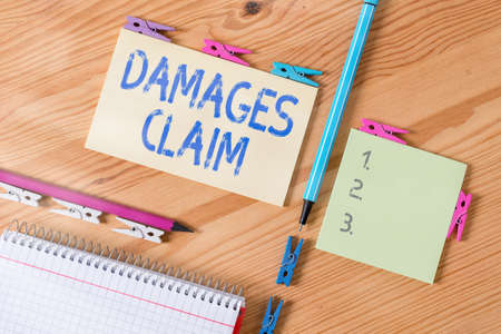 Conceptual hand writing showing Damages Claim. Concept meaning seeks to repair the damages or liability of the victim party Colored crumpled papers wooden floor background clothespin 写真素材