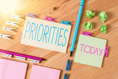 Handwriting text writing Priorities. Conceptual photo fact or condition of being regarded or treated as more important Colored clothespin papers empty reminder wooden floor background office