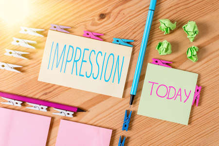Handwriting text writing Impression. Conceptual photo opinion about something especially form without conscious thought Colored clothespin papers empty reminder wooden floor background office Stock Photo