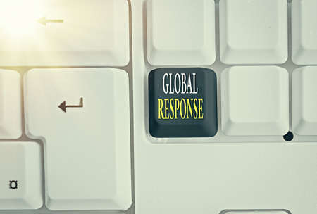 Conceptual hand writing showing Global Response. Concept meaning indicates the behaviour of material away from impact point Colored keyboard key with accessories arranged on copy space
