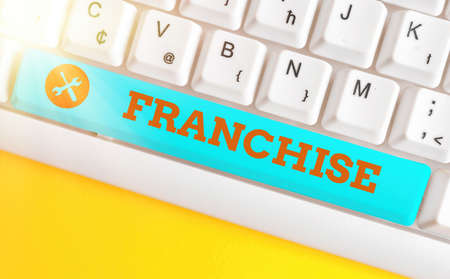 Handwriting text Franchise. Conceptual photo right or license granted to an individual or group to market Different colored keyboard key with accessories arranged on empty copy space