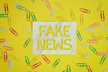 Word writing text Fake News. Business photo showcasing false information publish under the guise of being authentic news Flat lay above empty paper with copy space and colored paper clips