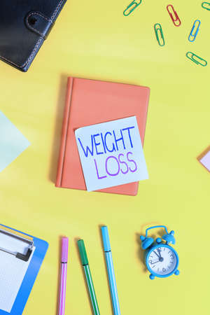Handwriting text writing Weight Loss. Conceptual photo a reduction of the total body mass due to a mean loss of fluid Flat lay above table with copy space paper clips clock and pencils