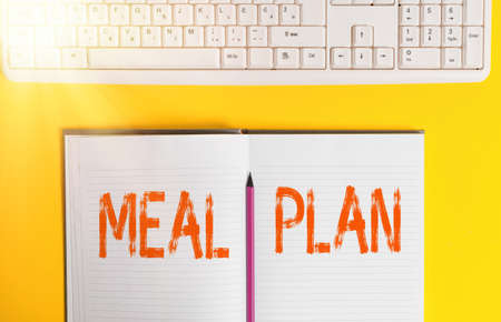 Handwriting text Meal Plan. Conceptual photo act of taking time to plan any number of meals for the week Copy space on notebook above yellow background with keyboard on table