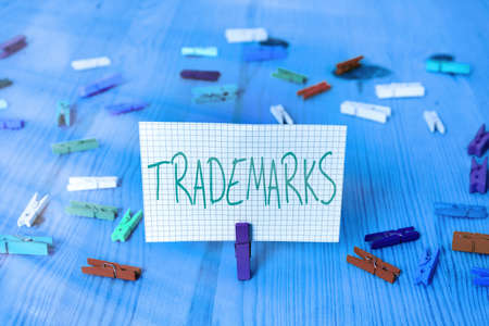 Conceptual hand writing showing Trademarks. Concept meaning legally reserved to the exclusive use of the owner as maker Colored crumpled rectangle shape paper light blue background